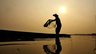 Silhouette of traditional fishermen throwing net fishing in the lake at sunrise time