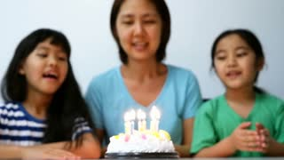 Slow motion happiness moment of Asian family blowing birthday candles