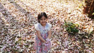 Slow Motion Happy Little Asian Girl Throws Flowers In The Air