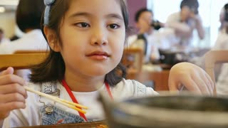 Slow motion of Asian girl eating Ramen noodle Japanese food in a restaurant.