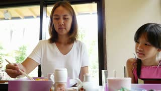 Slow motion of Asian mother feeding sushi for her daughter in a restaurant with smile face, Happy asian family concept
