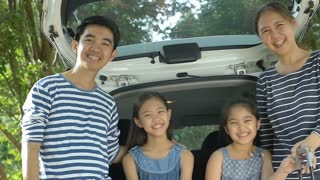 Slow motion of Happy Asian family on mini van are smiling and preparing for travel on vacation, Pan shot