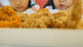Slow motion of Happy Asian girls with fried chicken in restaurant, Tilt up