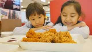 Slow motion of Happy Asian girls with fried chicken in restaurant, Zoom in