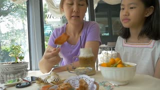Slow motion of Happy Asian mother and daughter enjoying with breakfast together in cafe