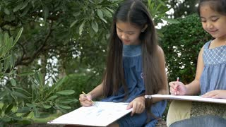 Slow motion of happy family, Asian girl sibling enjoy to painting and drawing in the park together