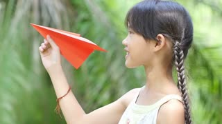Slow motion of little Asian child playing with paper airplane in the park