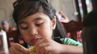 Slow motion of little Asian girl enjoy eating with seafood meal, Pan shot