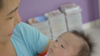 Slow motion of young Asian mother holding her newborn child, Family at home