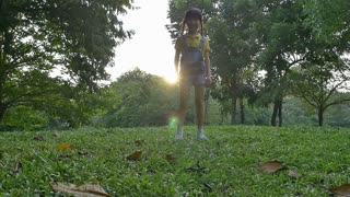 Slow motion shot : Happy Asian little girl jumping in the park