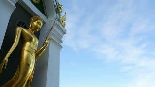Standing gold Buddha in Phitsanulok, Thailand : Pan shot