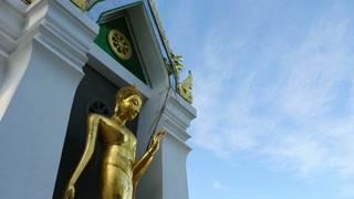 Standing gold Buddha in Phitsanulok, Thailand : Tilt down shot