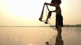 Unidentify fishermen throwing net fishing in the lake at sunrise time