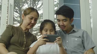 4K Asian daughter playing games on smart phone with parents, Happy time together