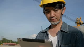 4K : Asian Engineer using digital tablet on construction site with blue sky