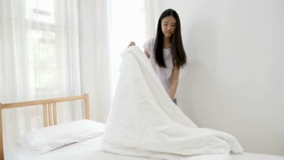 4K Asian girl cleaning bed room, making bed