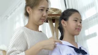 4K : Asian mother helping her's young daughter prepare to school