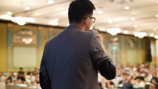 4K Asian professional coach speaking into the microphone on stage in auditorium