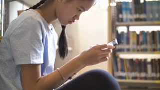 4K Asian teenager student using smart phone in school library for inspiration,Shoot wit natural light, Slow motion