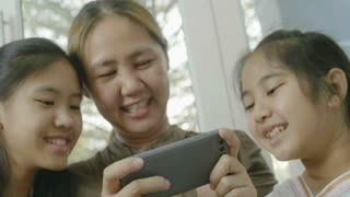 4K Asian woman playing games on smart phone with her daughters, Happy time together