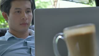 4K : Asian young business man bored in front of the laptop