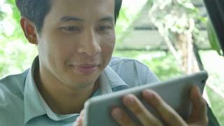 4K : Close up Asian young man using tablet pc, Pan shot