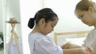 4K : Happy Asian daughter dressing her's uniform prepare to school with mother