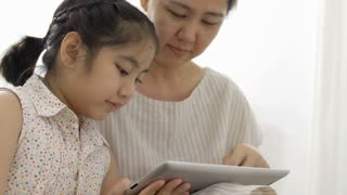 4K : Happy Asian girl playing digital tablet with her mother