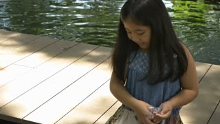 4K Happy Asian girl playing with fancy carp fish in the pond