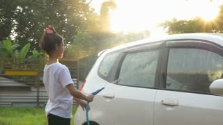 4K : Happy Asian girl washing car on water splashing and sunlight at home