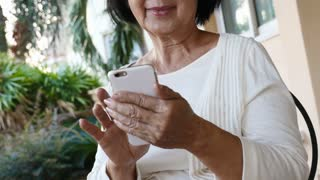 4K : Happy Asian senior woman using video call on smart phone, Tilt up shot