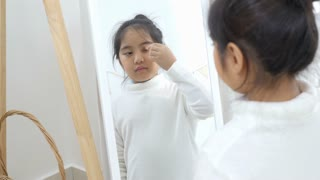4K : Little Asian child blushing her face by herself at home with makeup accessories