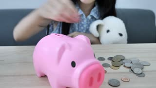 4K Little Asian girl putting money coin into piggy bank on wooden table, Save for the future.
