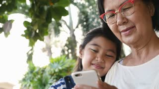 4K : Little Asian girl using smart phone with her grandmother