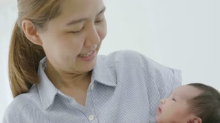4K Slow motion Happy Asian mother playing with her newborn baby daughter at home, Happiness moment of Asian family