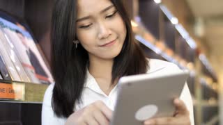 4K Slow motion : Happy Beautiful Asian student girl using digital tablet in library