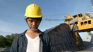 4K : Slow motion of Asian Engineer on construction site with blue sky