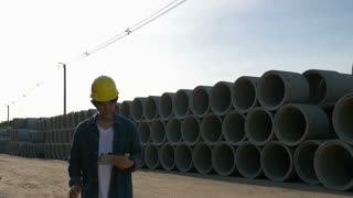 4K : Slow motion of Asian Engineer walking on construction site with blue sky