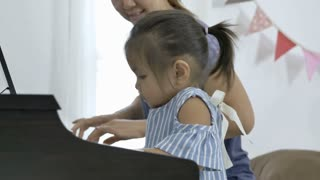 4K : Slow motion of Asian girl playing piano with her mother, Tilt up shot
