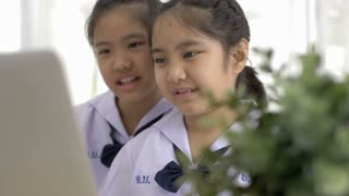 4K : Slow motion of Asian student in uniform using laptop computer together