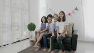4K : Slow motion of happy Asian family watching television together, Zoom out shot