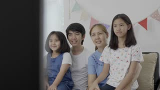 4K : Slow motion of happy Asian family watching television together