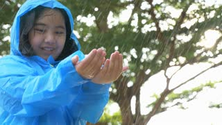 4K : Slow motion of Happy little Asian girl playing and smiling in the rain