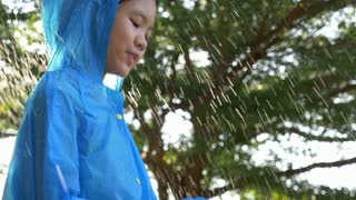 4K : Slow motion of Happy little Asian girl smiling in the rain, Feel free of nature in rainy season