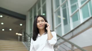 4K Slow motion of young Asian businesswoman wearing white shirt and using smart phone while walking out of office building