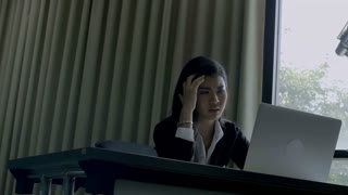 4K : Stressed Asian young woman who is working on a laptop computer, Pan shot