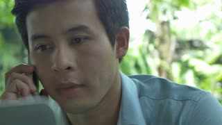 4K : Young Asian business man using laptop and talking with smart phone in cafe