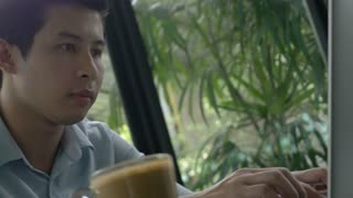 4K : Young Asian business man using laptop in coffee cafe