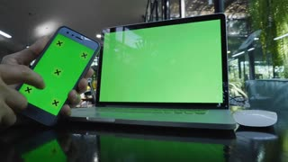 Close up man hands touching smart phone and using laptop with green screen