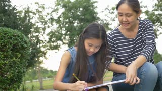 Happy Asian Daughter drawing picture with mother together in the park, Pan shot
